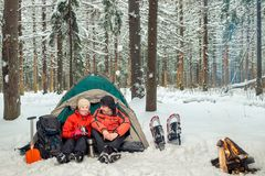 Man and woman active tourists, campground in the winter. Man and women active tourists, campground in the winter forest Royalty Free Stock Images