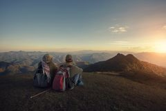 Man and woman backpacker sitting on top of high moutain with pan Royalty Free Stock Images