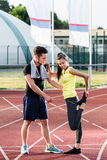 Man and woman on cinder track of sports arena stretching exercis Royalty Free Stock Photo