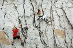 Man and women climbing. Cliff stock photography
