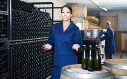 Man and women coworkers looking at bubbly wine in bottle standin Stock Image