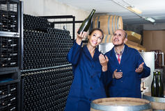 Man and women coworkers looking at bubbly wine in bottle standin Royalty Free Stock Photography