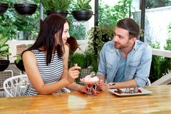 Young beautiful guy girl white cafe green leaves happy couple relaxing summer cafe love story communication. Man and women on a date in a cafe hold hands. Happy Royalty Free Stock Images