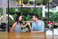 Young beautiful guy girl white cafe green leaves happy couple relaxing summer cafe love story communication. Man and women on a date in a cafe hold hands. Happy Stock Photo