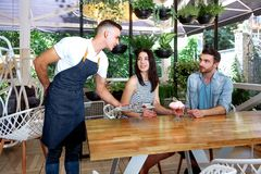 Young beautiful guy girl white cafe green leaves happy couple relaxing summer cafe love story communication. Man and women on a date in a cafe hold hands. Happy Royalty Free Stock Photography
