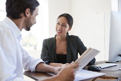 Man and woman with documents in an office, smiling, close up Royalty Free Stock Photos