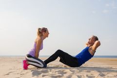 Man and woman doing fitness exercises together outdoors royalty free stock images