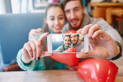 Couple in love making selfie in Valentines day. Man and women doing selfie with balloon in the form of heart in a cafe. Two people communicate, laughing and royalty free stock image
