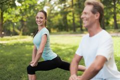 Man and woman doing warm-up in nature. Couple doing sports in nature. Stock Photography
