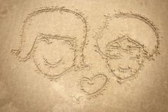 Man and women drawing on the sand Royalty Free Stock Photo