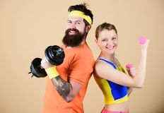 Man and woman exercising with dumbbells. Fitness exercises with dumbbells. Workout with dumbbells. Girl and guy hold royalty free stock image