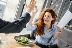 Businesspeople having business lunch at restaurant sitting eating salad drinking wine woman close-up giving five to royalty free stock photo