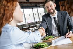 Businesspeople having business lunch at restaurant sitting eating salad drinking wine shaking hands making deal happy royalty free stock photography