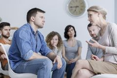 Discussion in support group. Man and women having a discussion in caucasian support group stock photos