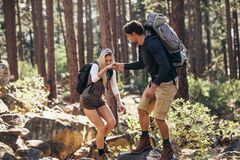 Hiking couple walking on rocks in forest wearing backpacks Royalty Free Stock Photography