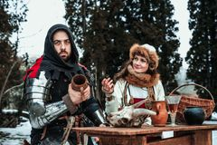 A man and a woman in historical costumes are sitting at a table stock image