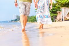Man and women hold one`s hand on the  beach and front of sunset. they are couple. they are walking on the sand and water stock images