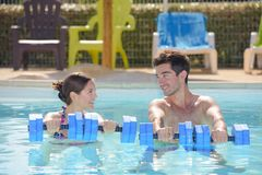 Man and woman holding floats in swimming pool royalty free stock image