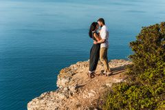 Couple in love hugging on a rock by the sea royalty free stock images
