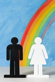 Man and women icons with a rainbow and blue sky Stock Photo