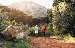 Athletic couple running together in a park Stock Images