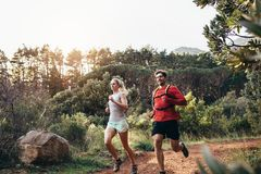 Athletic couple running together in a park Stock Photography