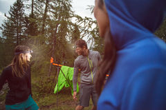 Man and woman joking and smiling with headlamp in evening near camping. Group of friends people summer adventure journey. Man and women joking and smiling with stock photography