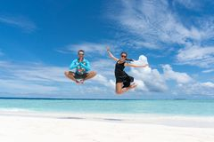 Man and woman jump on beach with transparent water of ocean in Maldives