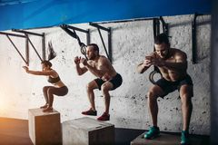 Group of man and woman jumping on fit box at gym Stock Images