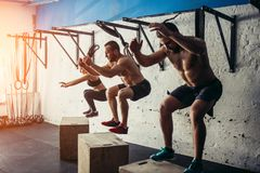 Group of man and woman jumping on fit box at gym Royalty Free Stock Photography
