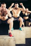 Group of man and woman jumping on fit box at gym Stock Photo