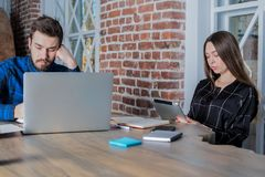 Two university students learning on-line via net-book and digital tablet, sitting in co-working space royalty free stock photos