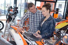 Man and woman in motorcycle concessionary showroom Royalty Free Stock Photo