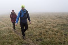 Man and woman on the mountains meadow in the fog stock photos