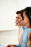 Man and women operator working with headphones Stock Photography