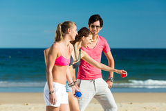 Man and women playing boule on beach Royalty Free Stock Image