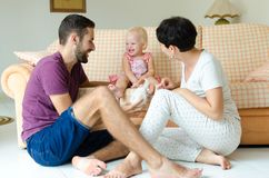 Man and woman playing with a child. Young family at home on the weekend. Man and women playing with a child. Young family at home on the weekend stock photography