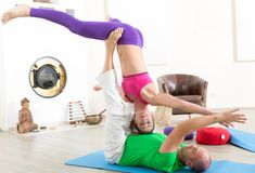 Couple practicing acroyoga. Man and women practicing pair yoga in morning stock image