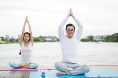 Man and woman practicing yoga and meditation on mat near lagoon. health concept. royalty free stock image