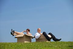 Man and women relaxing in cardboard box Stock Photos