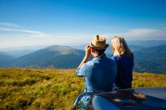 Enjoy the mountain view. Man and a women rely on the hood of an automobile looking into binoculars and enjoying the landscape Royalty Free Stock Images