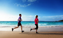 Man and women running on tropical beach Stock Photo