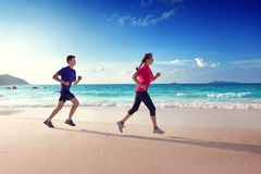 Man and women running on tropical beach Stock Photos