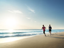 Man and women running on tropical beach at sunset Stock Images
