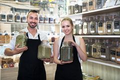 Sellers posing with banks of dried herbs in store. Man and women sellers posing with banks of dried herbs in store royalty free stock images