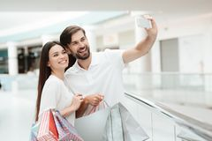 Man and woman in shopping mall. Couple is taking selfie on phone. stock photo