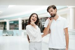 Man and woman in shopping mall. Woman wants to go to store but man is tired. stock photography