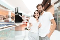 Man and woman in shopping mall. Couple is taking selfie with selfie stick. Man and women in shopping mall. Couple is taking selfie with selfie stick. Couple is royalty free stock image