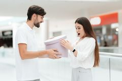 Man and woman in shopping mall. Man presents woman with new round box. royalty free stock photos