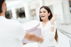 Man and woman in shopping mall. Man presents woman with new round box. royalty free stock photo